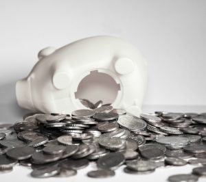 piggy bank on side with coins spilling out