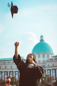 A woman throws her graduation cap into the air