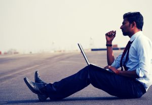 a man sits on the side of the road with an open laptop