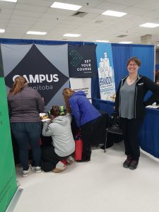 A Campus Manitoba employee smiles for the camera while students fill out ballots.