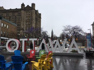 The city of ottawa sign with colourful chairs infront of it.