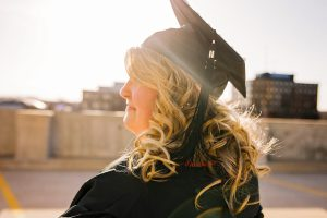 A young woman stands in a cap and gown at her graduation