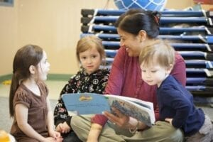 Woman sitting and reading to three kids