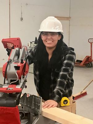 A student from Peguis First Nation stands in front of a power tool.