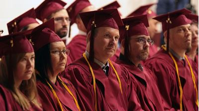 A row of graduates listen attentively