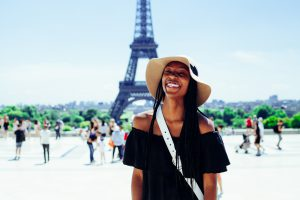 Woman working abroad standing in front of Eiffel Tower.