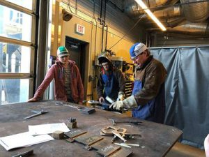 High school students learning from a tradesman.