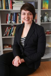 Dr. Corinne L. Mason sitting in front of bookshelf