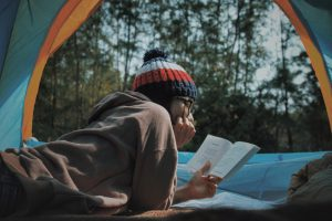 woman in toque lying in nature reading  a book