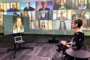 a woman looking leading a virtual meeting looking at screens with faces